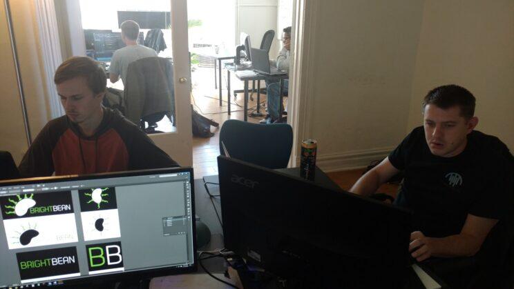 people sitting at desks working at desktop computers
